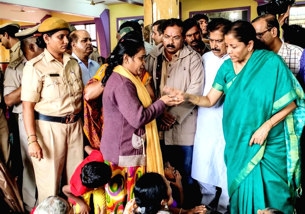 Union Finance and Corporate Affairs Minister Nirmala Sithraman interacts with a flood victim during her visit to a relief camp in Karnataka's Belagavi on Aug 10, 2019. - Nirmala Sithraman