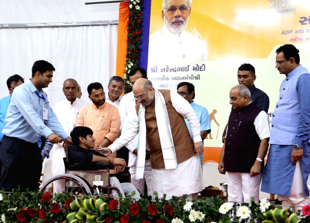 Union Home Minister Amit Shah distributes supportive equipment to a Divyang or physically challenged at Samajik Adhikarita Shivir in Kalol of Gujarat's Gandhinagar district on Oct 25, ... - Amit Shah and Nitinbhai Patel
