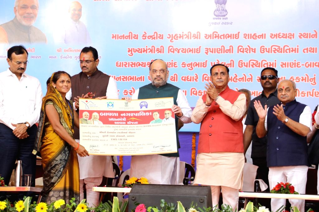 Union Home Minister Amit Shah distributes the approval letters to the beneficiaries of various government development schemes of Sanand and Bavla assembly constituencies, in Gujarat's ... - Amit Shah and Nitinbhai Patel