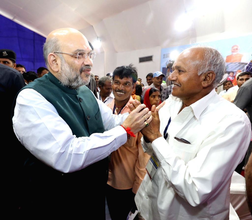 Union Home Minister Amit Shah interacts with a beneficiary of Ayushman Bharat Yojana in Gujarat's Ahmedabad on Oct 26, 2019. - Amit Shah