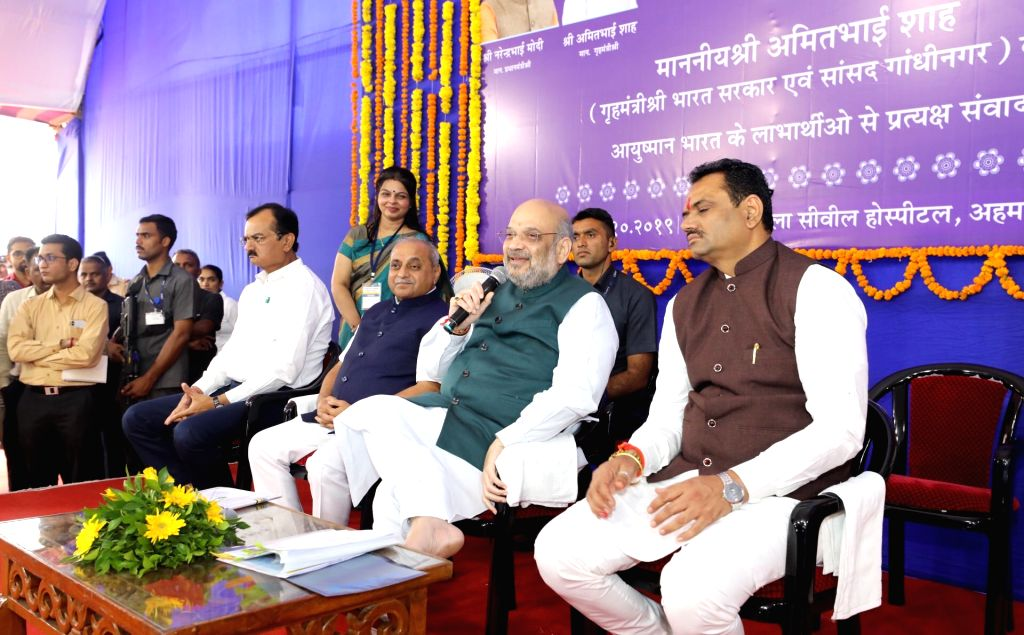Union Home Minister Amit Shah interacts with the beneficiaries of Ayushman Bharat Yojana in Gujarat's Ahmedabad on Oct 26, 2019. Also seen Gujarat Deputy Chief Minister Nitinbhai Patel. - Amit Shah and Nitinbhai Patel