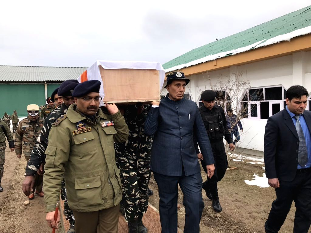 Union Home Minister Rajnath Singh lifts the coffin of one of the one of the 45 CRPF personnel killed in a suicide attack by militants in Jammu and Kashmir's Pulwama district on 14th Feb 2019; in Budgam of Jammu and Kashmir, on Feb 15, 2019. (Photo: @ - Rajnath Singh