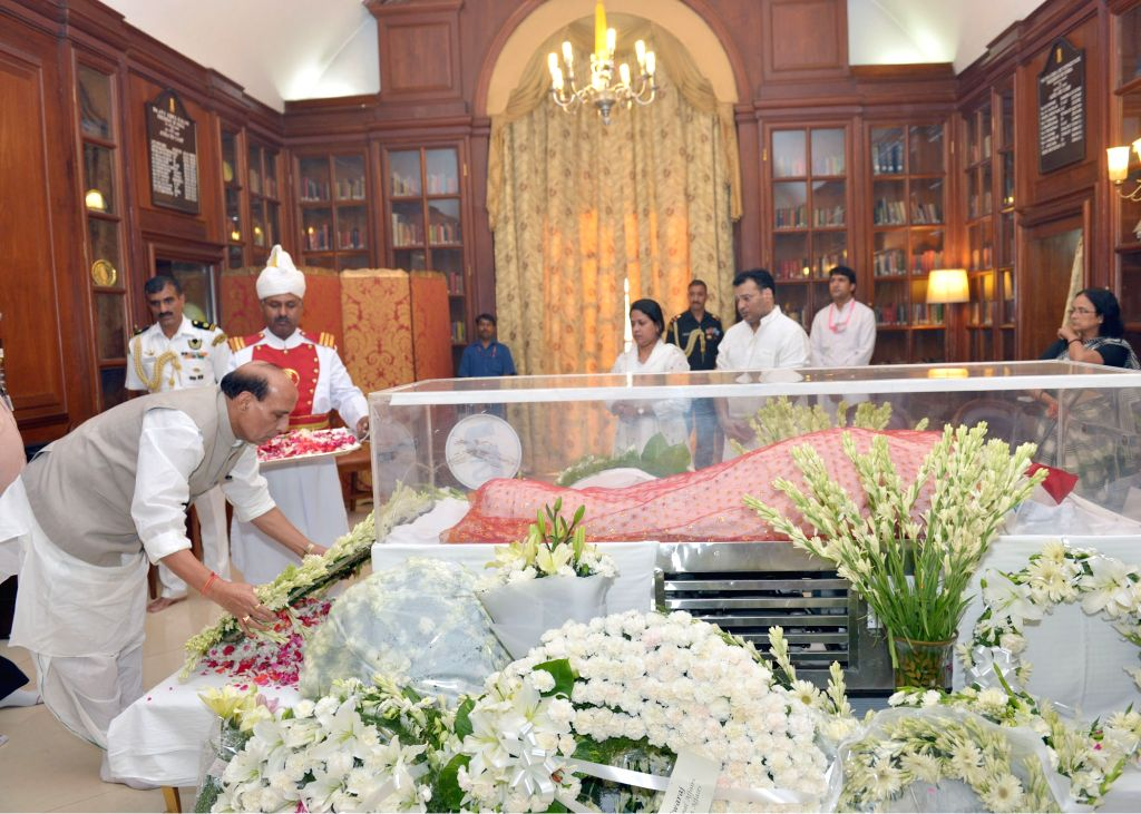 Union Home Minister Rajnath Singh pays tribute to the mortal remains of President Pranab Mukherjee's wife Suvra at Rashtrapati Bhawan on Aug 18, 2015. - Rajnath Singh and Pranab Mukherjee