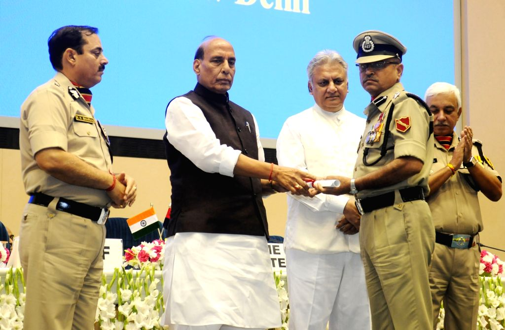 Union Home Minister Rajnath Singh presents awards, at the Investiture Ceremony of Border Security Force (BSF), in New Delhi on May 22, 2018. Also seen BSF DG K.K. Sharma and Intelligence ... - Rajnath Singh, K. Sharma and Rajiv Jain