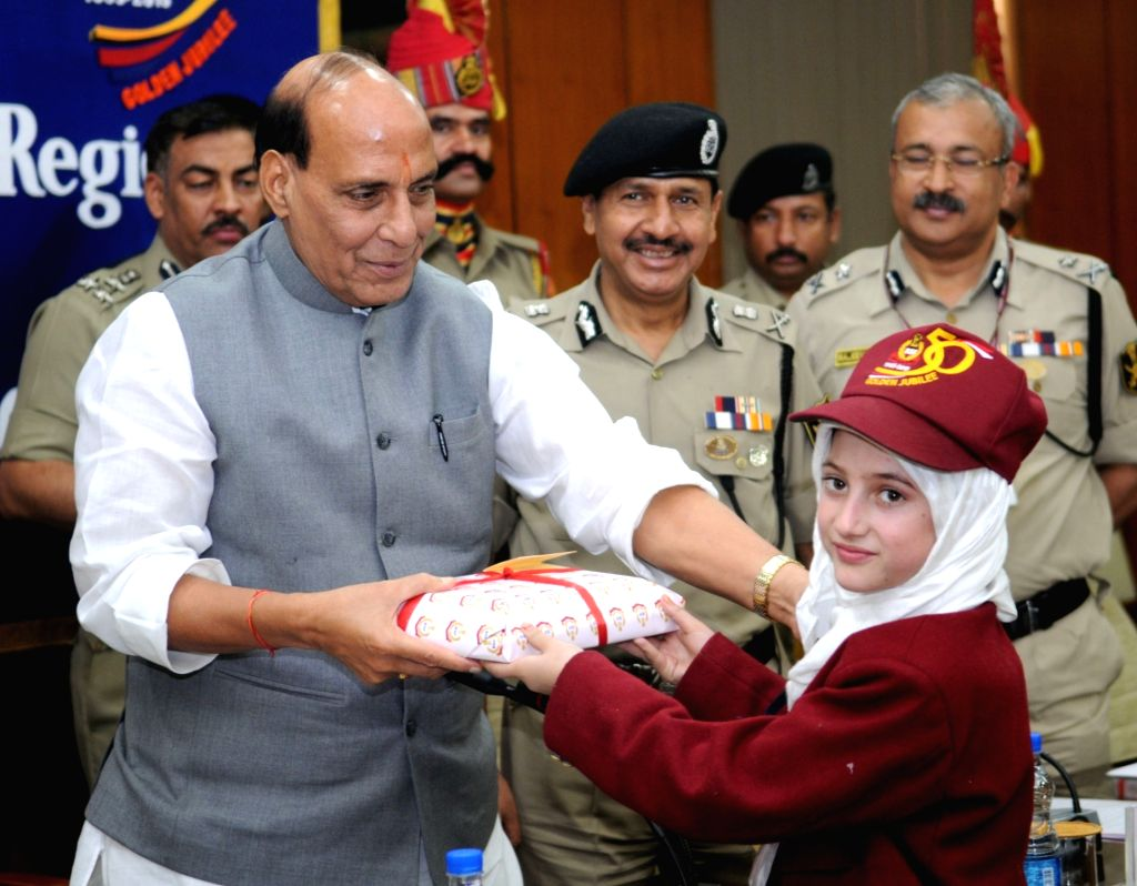 Union Home Minister Rajnath Singh presents gift to a child from Kashmir region who is on a Border Security Force conducted Bharat Darshan tour, in New Delhi on Nov 13, 2015. Also seen BSF ... - D K Pathak