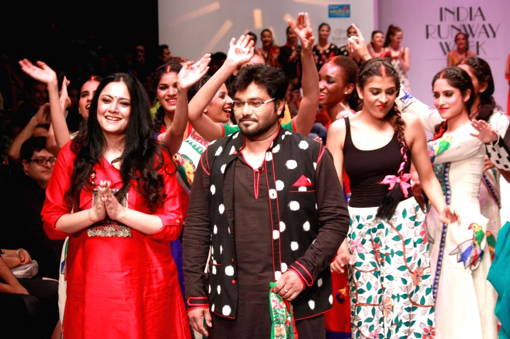 Union Minister and singer Babul Supriyo walks the ramp showcasing fashion designer Agnimitra Paul (in red dress) during ​India Runway Week in New Delhi, on April 17, 2016.