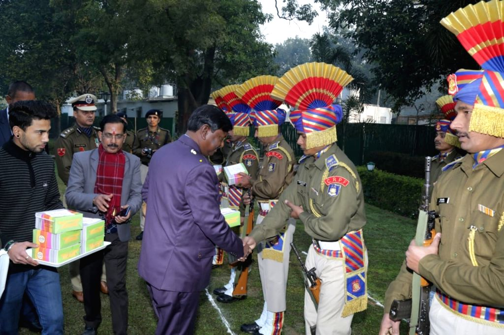 Union Minister Arjun Munda distributes sweets among CRPF personnel after hoisting the National Flag on the occasion of India's 71st Republic Day, in New Delhi on Jan 26, 2020. - Arjun Munda