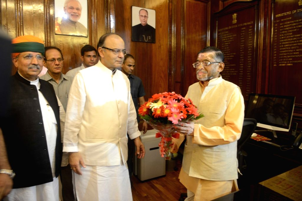 Union Minister for Finance and Corporate Affairs Arun Jaitley greets Santosh Kumar Gangwar and Arjun Ram Meghwal as they take charge as the Ministers of State for Finance, in New Delhi on ... - Affairs Arun Jaitley and Santosh Kumar Gangwar