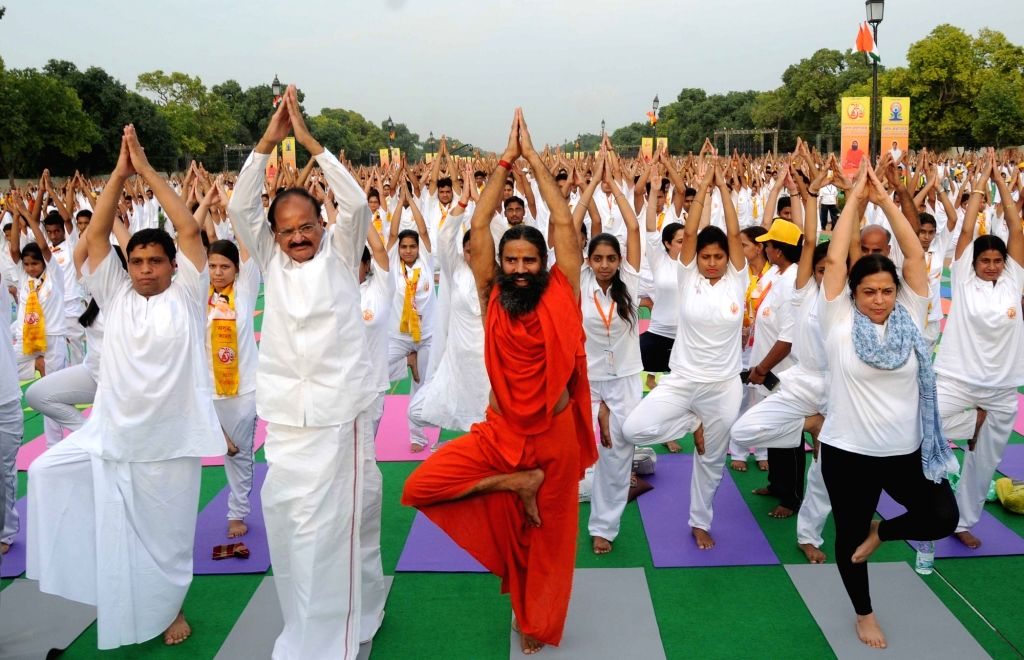 Union Minister for Urban Development, Housing and Urban Poverty Alleviation and Parliamentary Affairs M Venkaiah Naidu with Yoga Guru Ramdev during a Yoga programme ahead of International ... - Venkaiah Naidu