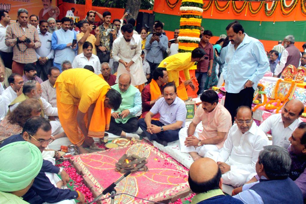 Union Minister Harsh Vardhan and BJP leaders Vijender Gupta, Manoj Tiwari and Vijay Goel participate in rituals performed as part of ???bhoomi pujan??? organised by the BJP ahead of the ... - Harsh Vardhan and Vijender Gupta