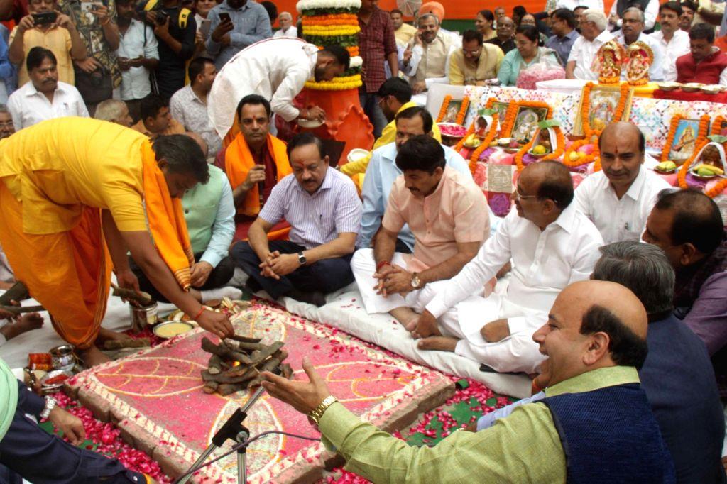 Union Minister Harsh Vardhan and BJP leaders Manoj Tiwari and Vijay Goel participate in rituals performed as part of ???bhoomi pujan??? organised by the BJP ahead of the upcoming Delhi ... - Harsh Vardhan