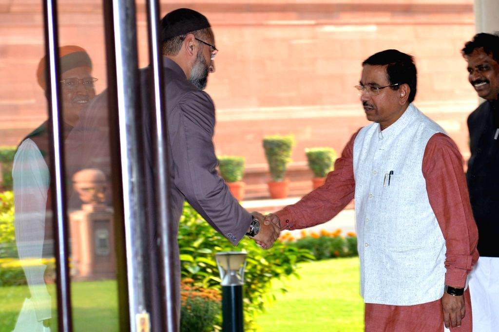 Union Minister Pralhad Joshi and AIMIM MP Asaduddin Owaisi greet each other as they arrive to attend an all-party meeting called by Lok Sabha Speaker Om Birla ahead of the Winter Session ... - Pralhad Joshi