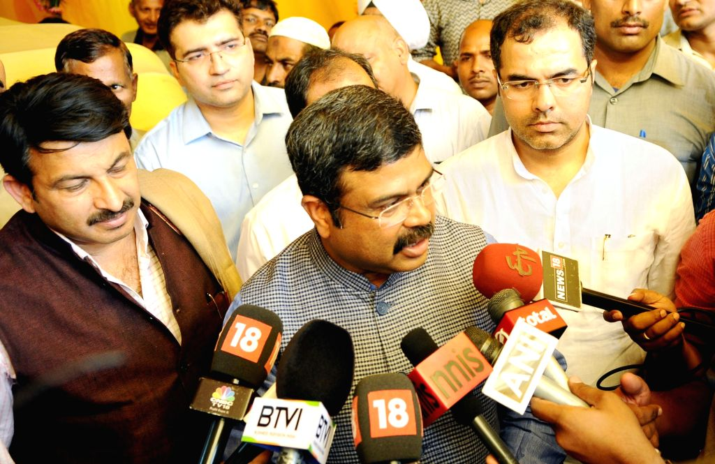 Union Petroleum Minister Dharmendra Pradhan talks to the press after launching the IGL smart card, prepaid CNG cards for both retail and fleet customers in New Delhi on Oct 11, 2017. Also ... - Dharmendra Pradhan and Pravesh Verma
