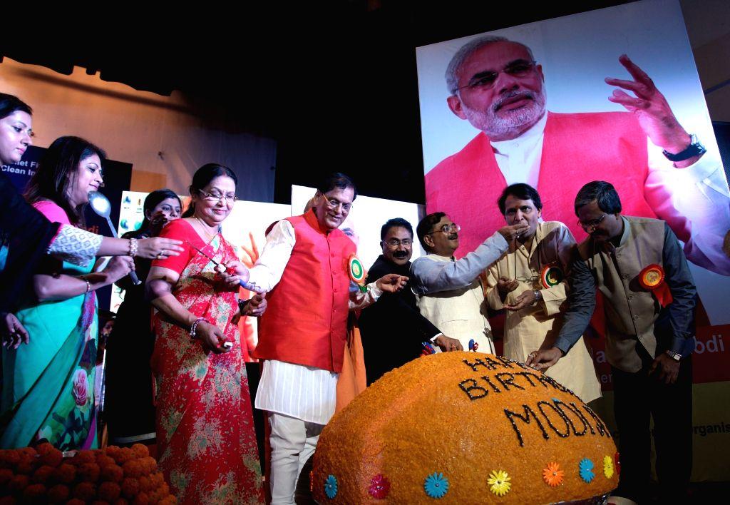 Union Railway Minister Suresh Prabhakar Prabhu unveils a 500kg Laddu at the inauguration of Swachh Diwas to mark the birthday of Prime Minister Narendra Modi in New Delhi on Sept 17, 2016. - Suresh Prabhakar Prabhu and Narendra Modi