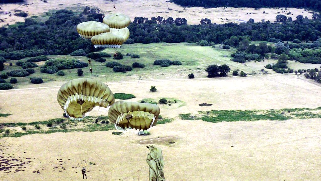United Kingdom: Parachutes of IAF Special Forces Garud Commandos opening up on exit from the RAF Hercules during a para drop over a DZ in the United Kingdom.