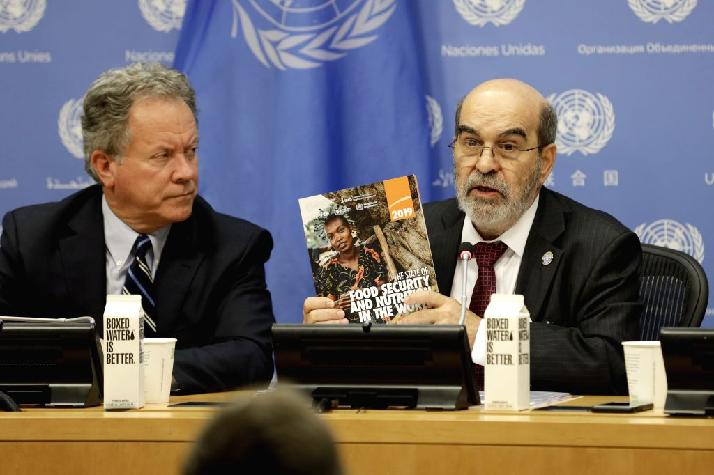 """UNITED NATIONS, July 15, 2019 - Jose Graziano da Silva (R), Director-General of the United Nations Food and Agriculture Organization (FAO), holds a copy of the newly launched report """"The State ..."""