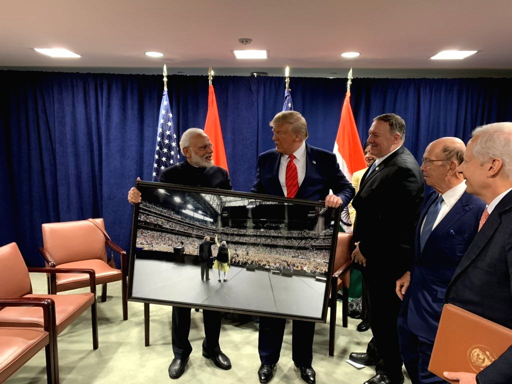 """United Nations: Prime Minister Narendra Modi presents a framed photograph from the """"Howdy Modi"""" event to US President Donald Trump during a meeting on the sidelines of the UNGA74 at United ... - Narendra Modi"""