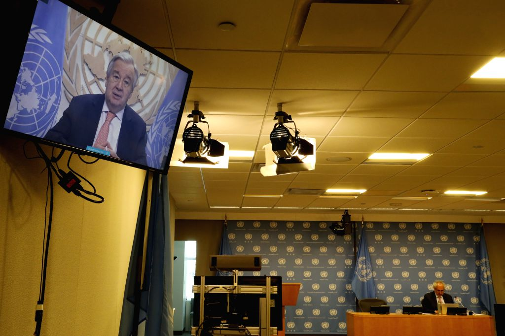 United Nations Secretary-General Antonio Guterres (on the screen) speaks at a virtual press briefing at the UN headquarters in New York, on June 25, 2020. ...
