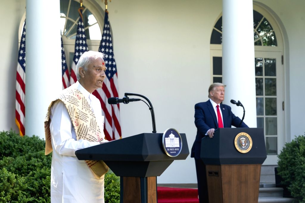 United States President Donald Trump listens as Pujari Harish Brahmbhatt, BAPS Shri Swaminarayan Mandir, Robbinsville, delivers remarks during the White House National Day of Prayer Service on Thursday, May 7, 2020, in the Rose Garden of the White Ho