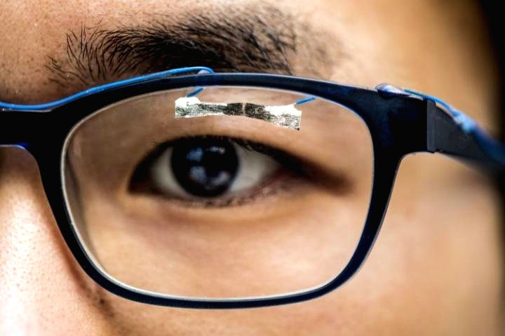 University of Washington graduate student, Jinyuan Zhang, demonstrates how wearable sensors can track eye movement. (Credit: Dennis R. Wise/University of Washington)