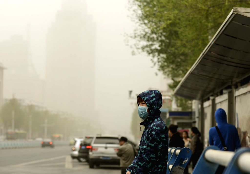 A man wearing a mask waits for bus in Urumqi, capital of northwest China's Xinjiang Uygur Autonomous Region, April 27, 2015. A sandstorm hit the region on Monday, ...