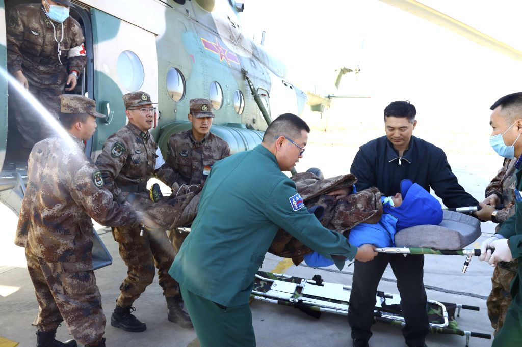 URUMQI, April 9, 2019 - An injured person is carried down from a helicopter after being rescued in Urumqi, northwest China's Xinjiang Uygur Autonomous Region, April 9, 2019. Ten people have been ...
