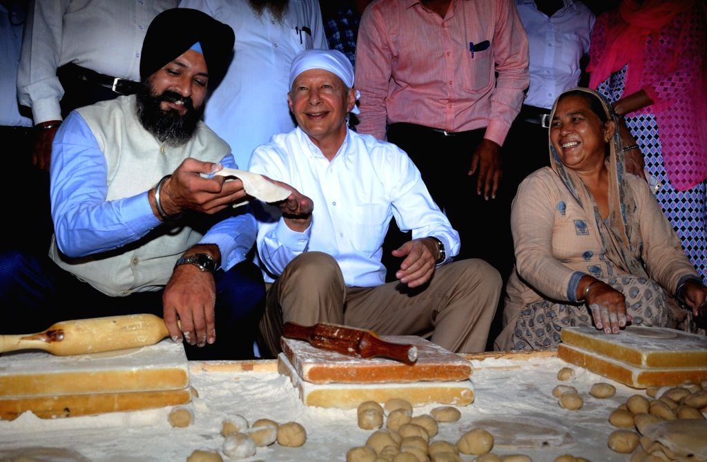 US Ambassador to India Kenneth I. Juster helps in preparing 'Guru Ka Langar' during his visit to the Golden Temple, in Amritsar on Oct 24, 2018.