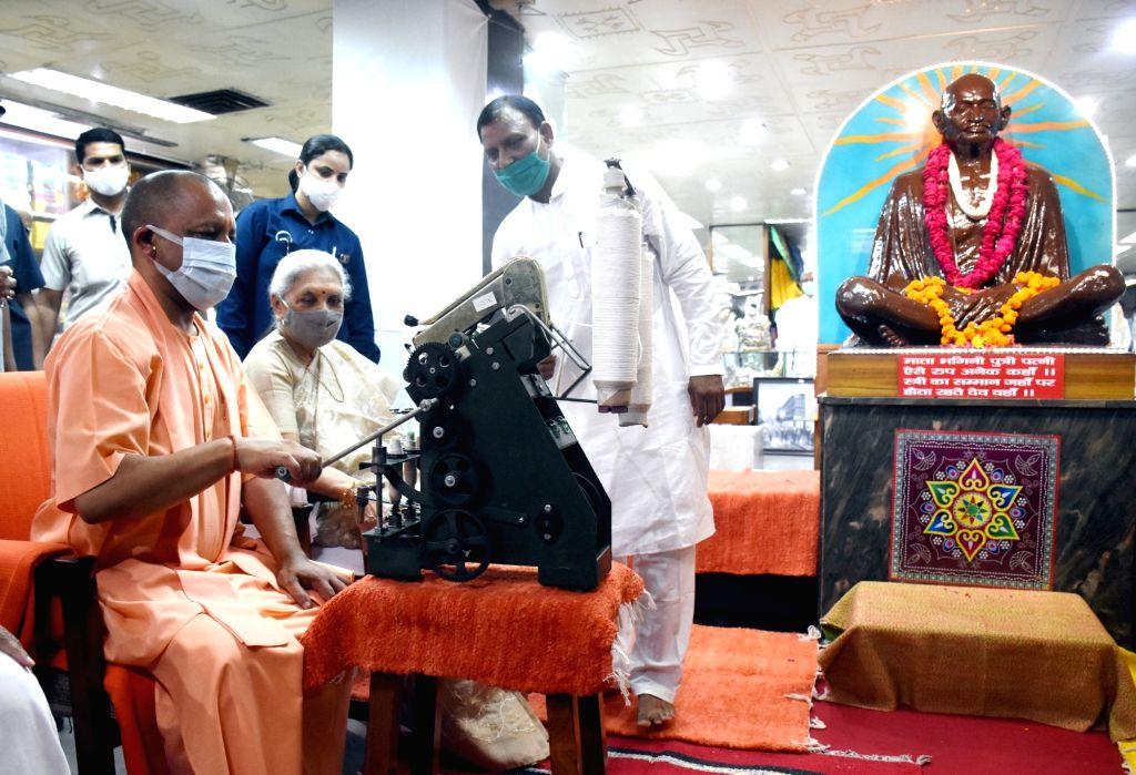 Uttar Pradesh Chief Minister Yogi Adityanath spins the charkha at Gandhi Ashram on the Birth Anniversary of Mahatma Gandhi in Lucknow on Saturday October 02,2021 - Yogi Adityanath