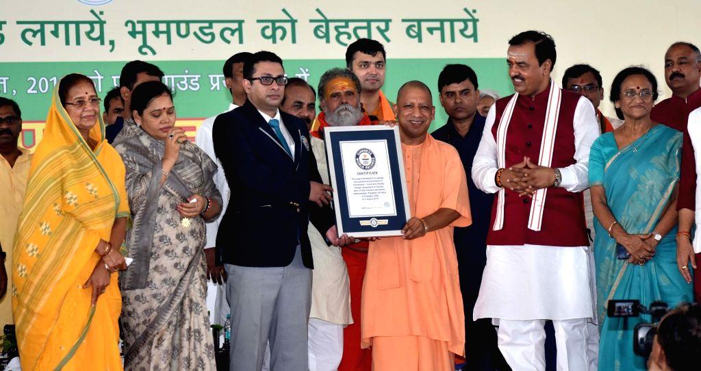 Uttar Pradesh Chief Minister Yogi Adityanath receives Guinness Book of World Record certificate after Uttar Pradesh entered the Record book for planting 10 lakh saplings within a span of ... - Yogi Adityanath
