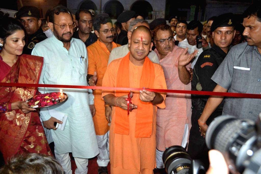 Uttar Pradesh Chief Minister Yogi Adityanath cuts the ribbon to inaugurate an exhibition depicting achievements of NDA government in last three years in Varanasi on May 27, 2017. - Yogi Adityanath