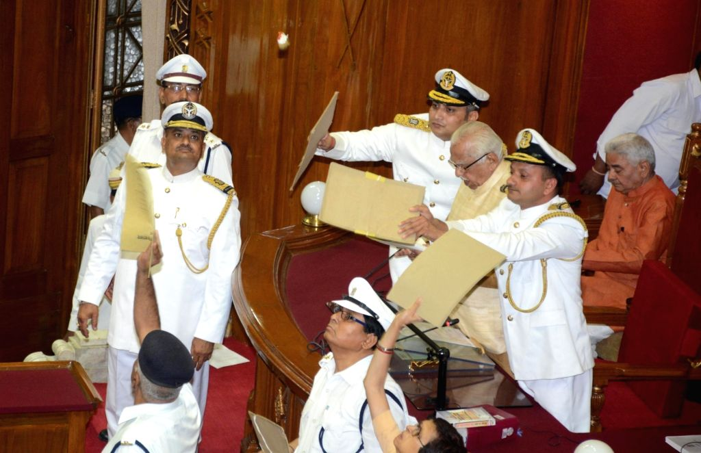 Uttar Pradesh Governor Ram Naik's security personnel shield him from the paper missiles being hurled at him from the opposition during the first sitting of the 17th Uttar Pradesh Assembly in ...