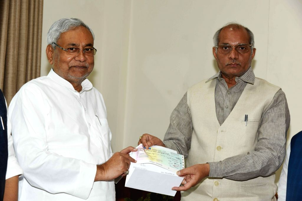 Uttar Pradesh Irrigation Minister Dharmpal Singh presents a cheque of 5 crores to Bihar Chief Minister Nitish Kumar as a contribution to the Chief Minister's Relief Fund in Patna on Sept 12, ... - Dharmpal Singh and Nitish Kumar