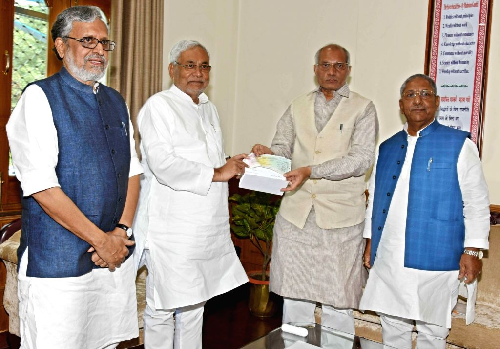 Uttar Pradesh Irrigation Minister Dharmpal Singh presents a cheque of 5 crores to Bihar Chief Minister Nitish Kumar as a contribution to the Chief Minister's Relief Fund in Patna on Sept 12, ... - Dharmpal Singh, Nitish Kumar and Sushil Kumar Modi