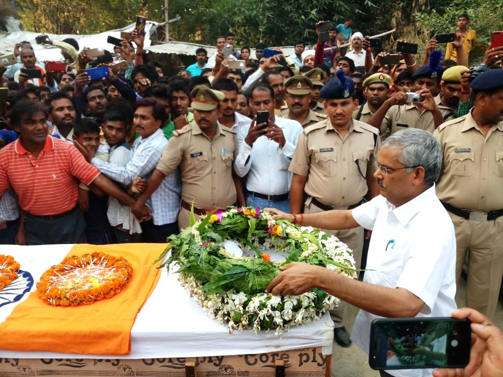 Uttar Pradesh Minister Neelkanth Tiwari lays wreath on Chhattisgarh Armed Force (CAF) trooper Ravinath Patel, in Varanasi on May 21, 2018. Patel was among the seven security personnel who ... - Neelkanth Tiwari and Ravinath Patel