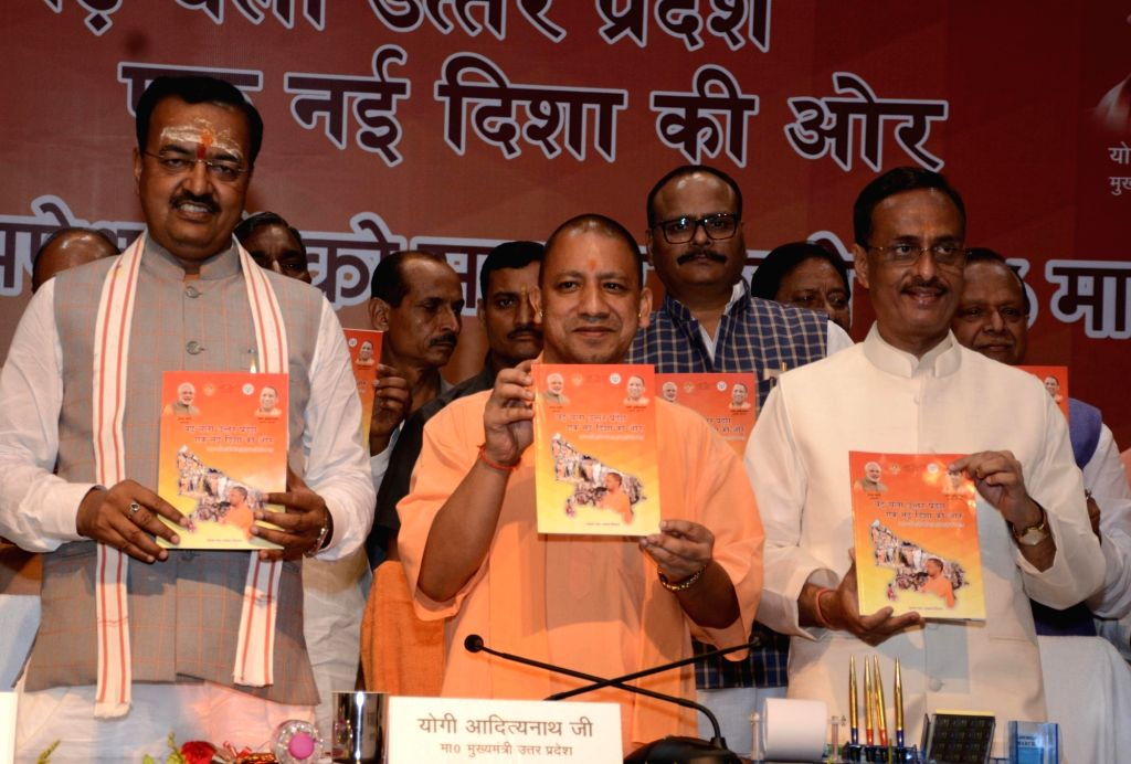 Uttar Pradesh (UP) Chief Minister Yogi Adityanath along with Deputy Chief Ministers Keshav Prasad Maurya and Dinesh Sharma, launches a book on the completion of his six months as CM in ... - Yogi Adityanath, Keshav Prasad Maurya and Dinesh Sharma