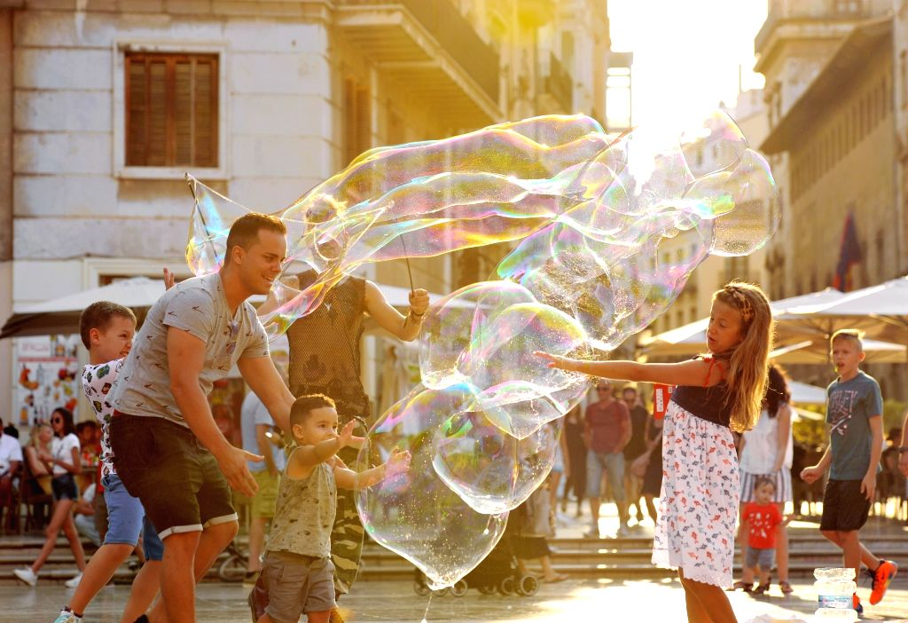 VALENCIA, July 16, 2019 - Children play with soap bubbles at a square in Valencia, Spain, July 14, 2019.