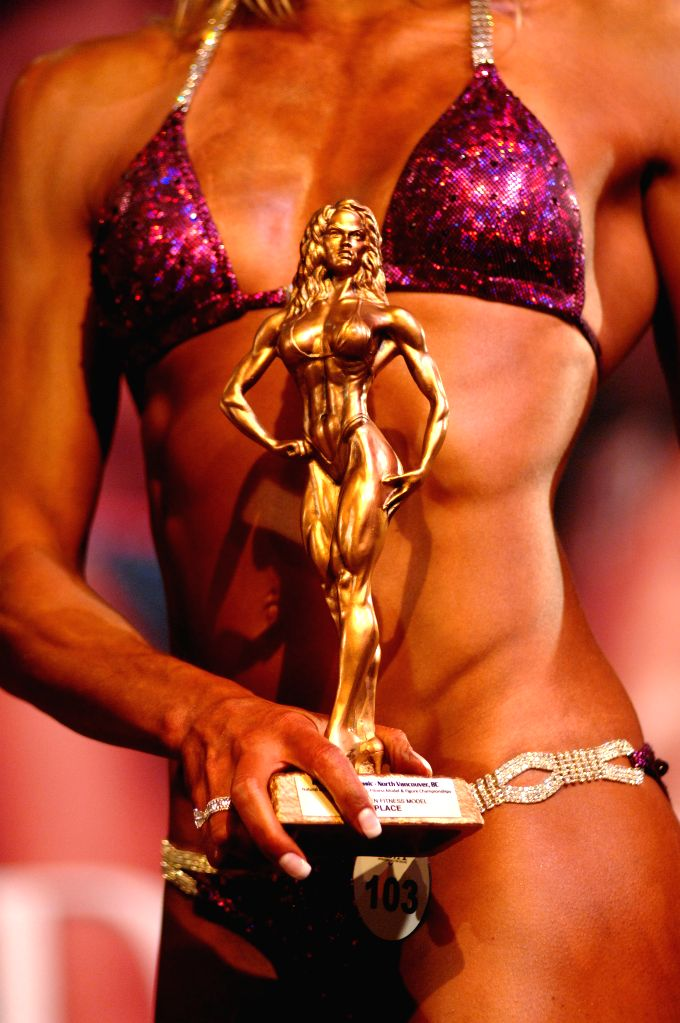 A female athlete holds a trophy after competing at the 2014 International Drug Free West Coast Classic Bodybuilding competition in North Vancouver, BC, Canada, Nov. 23, 2014. International