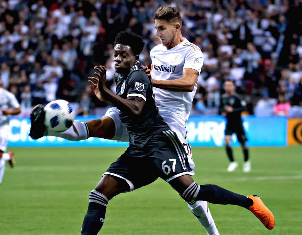 VANCOUVER, April 14, 2018 - Vancouver Whitecaps' Alphonso Davies (Front) vies with Los Angeles FC's Dejan Jakovic during the Major League Soccer (MLS) regular season soccer match between Vancouver ...