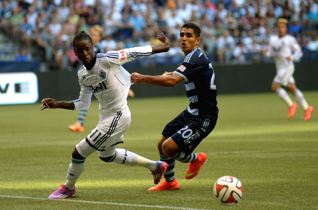 Sporting Kansas City's Jorge Claros (R) vies with Vancouver Whitecaps' Darren Mattocks during their MLS soccer game at BC Place in Vancouver, Canada, on Aug. 10, .
