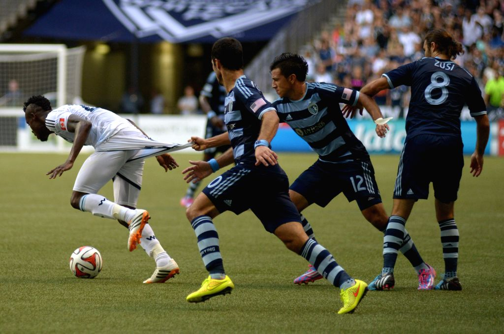 Vancouver Whitecaps' Gershon Koffie (L) vies with Sporting Kansas City's Mikey Lopez during their MLS soccer game at BC Place in Vancouver, Canada, on Aug. 10, ...