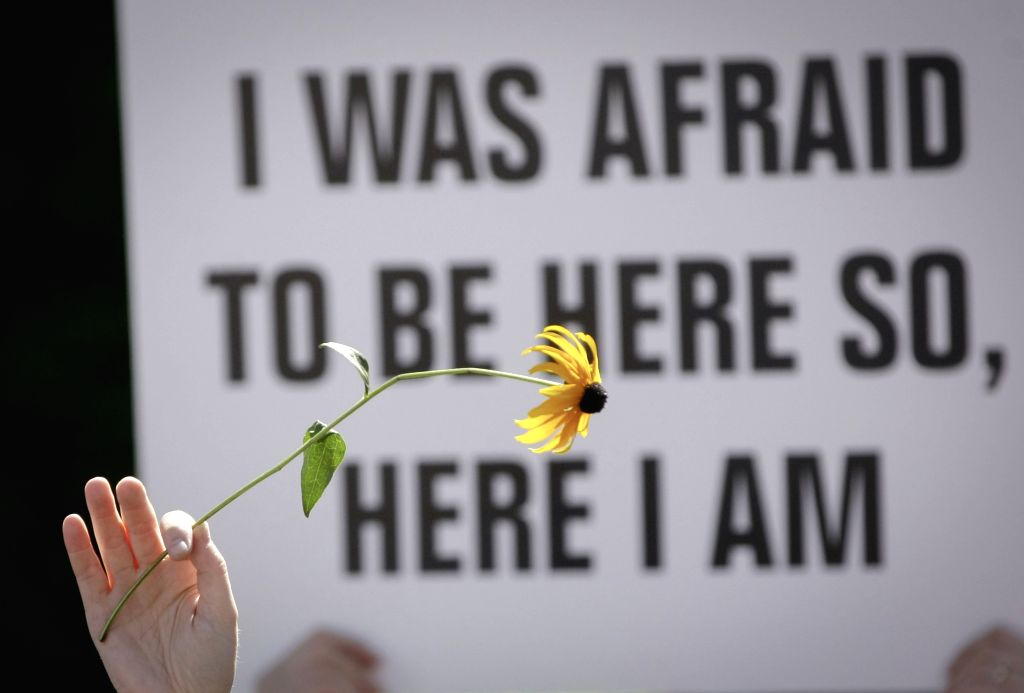 VANCOUVER, Aug. 20, 2017 - A protestor holds up a flower in front of a sign during an anti-racism rally outside Vancouver City Hall in Vancouver, Canada, Aug. 19, 2017.
