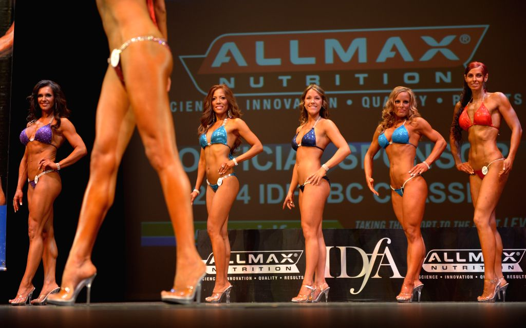 Female athletes compete during the 2014 International Drug Free Athletics (IDFA) BC Classic Bodybuilding competition in North Vancouver, BC, Canada, Aug. 23, ...