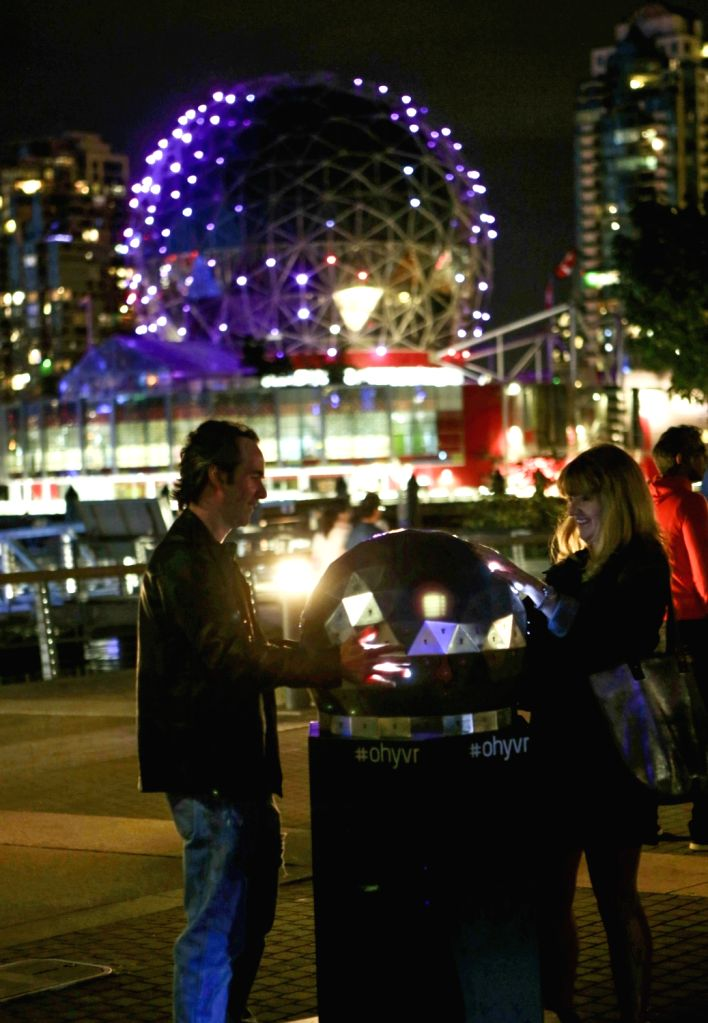 VANCOUVER, Aug. 4, 2018 - People try to change the light pattern of the Science World museum building by touching an interactive art device in Vancouver, Canada, Aug. 3, 2018. The interactive art ...