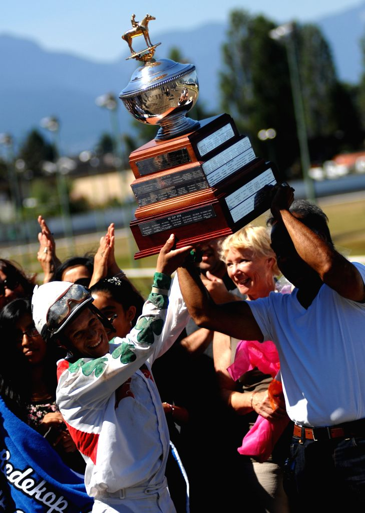Jockey Amadeo Perez (L Front) celebrates winning the race on Wilo Kat during the 2014 BC Cup horse racing at Hastings Park racecourse in Vancouver, Canada, Aug. 4,