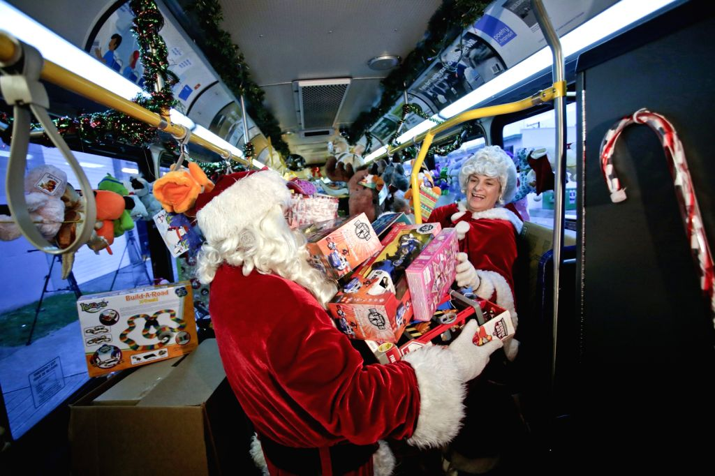 "VANCOUVER (CANADA), Dec.20, 2013 (Xinhua/IANS)Mr. and Mrs. Claus help unloading toys from a bus at the ""Toys for Tots"" drive in Vancouver, Canada, Dec. 19, 2013. Local bus company ..."
