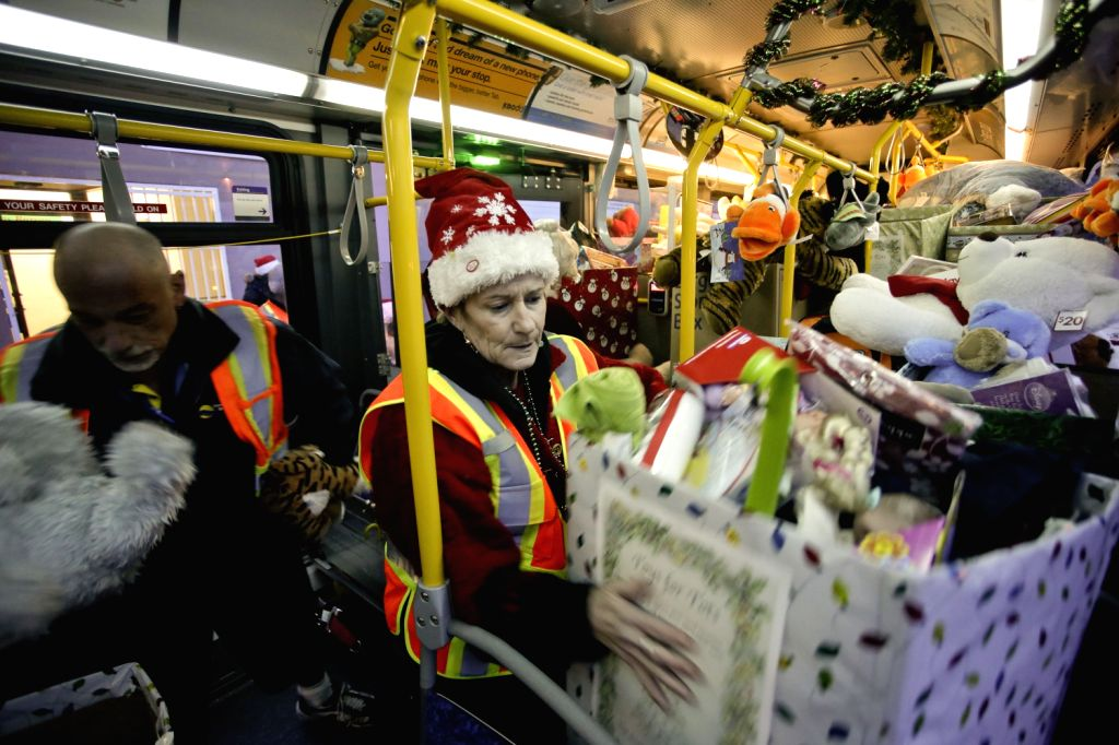 "VANCOUVER (CANADA), Dec.20, 2013 (Xinhua/IANS)Staffs from Coast Mountain bus company help unloading toys from a bus at the ""Toys for Tots"" drive in Vancouver, Canada, Dec. 19, ..."