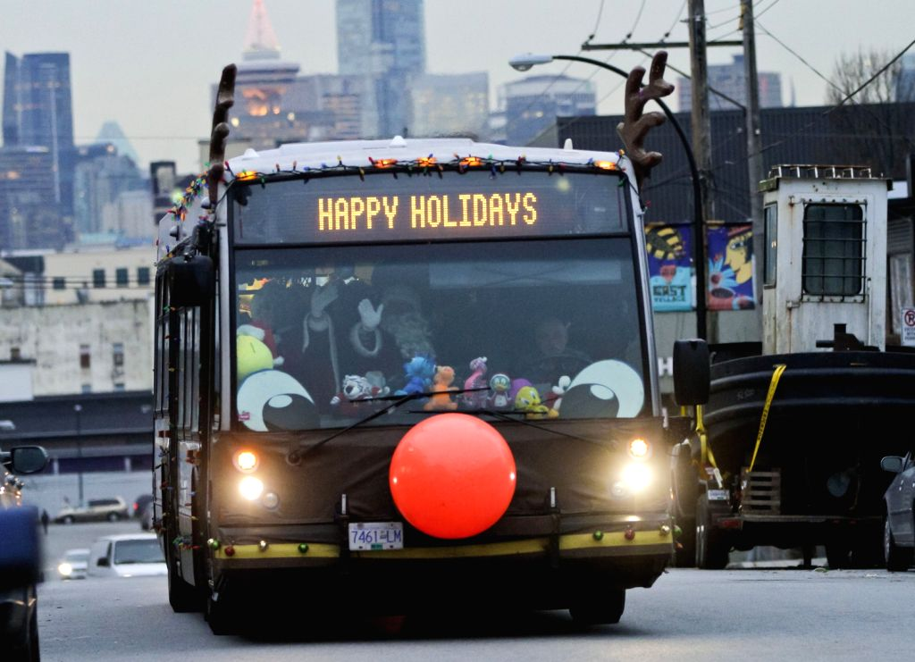 "VANCOUVER (CANADA), Dec.20, 2013 (Xinhua/IANS)Toys are delivered by a decorated bus at the ""Toys for Tots"" drive in Vancouver, Canada, Dec. 19, 2013.Local bus company follow it's .."