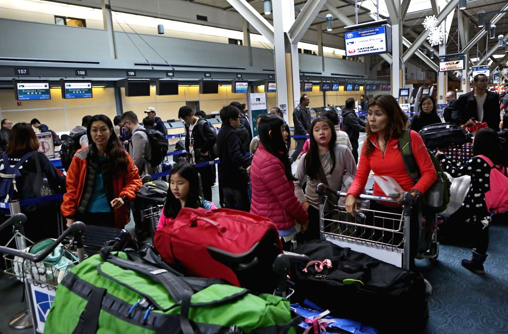 VANCOUVER (CANADA), Dec. 20, 2014 (Xinhua) -- Travellers wait for their flights at Vancouver international airport in Vancouver, Canada, Dec.19, 2014. Vancouver International Airport meets one of the busiest days with approaching winter holidays. (Xi