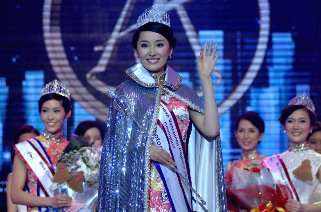Cindy Zhong (C) waves after being crowned the Miss Chinese Vancouver 2013 in Vancouver, Canada, on Dec. 12, 2013. She will represent Vancouver at Miss ...