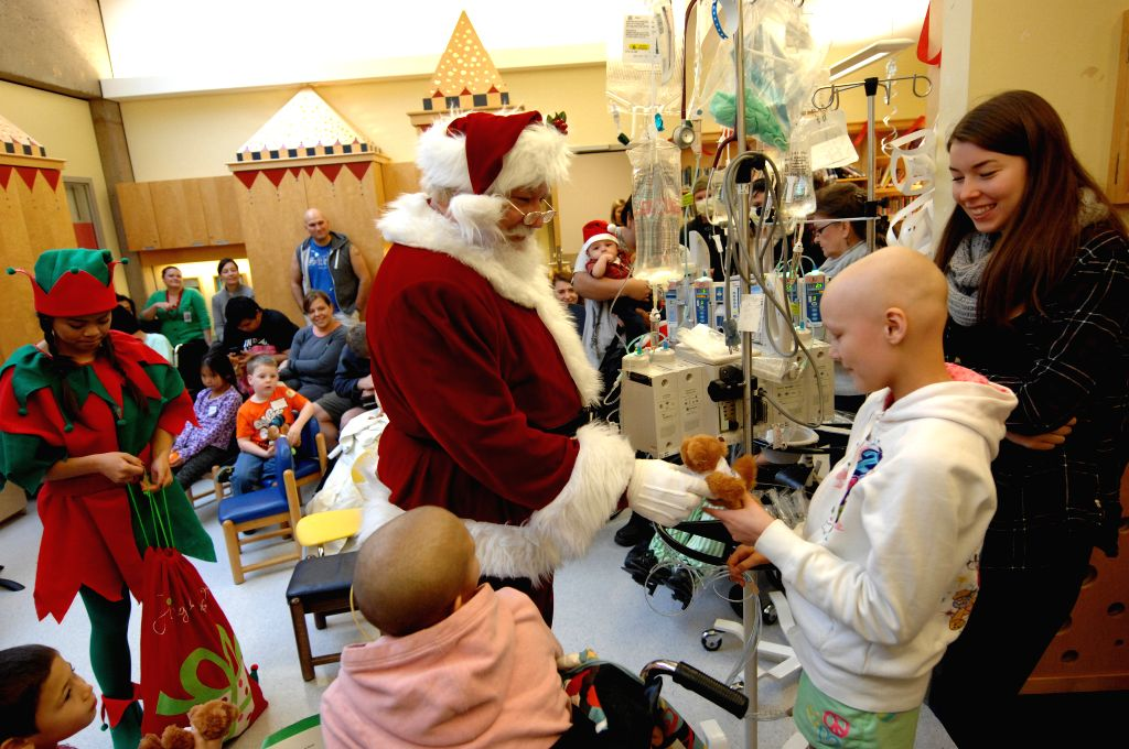 Kathlynn (2nd R) receives Christmas present from Santa Claus at BC Children's Hospital in Vancouver, Canada, Dec.16, 2014. BC Ambulance Service flew Santa Claus ..